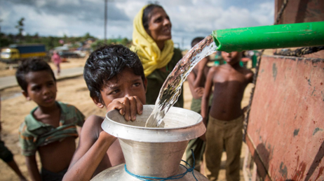 Rohingya refugee boy and others waiting for water as it is dispensed into a container