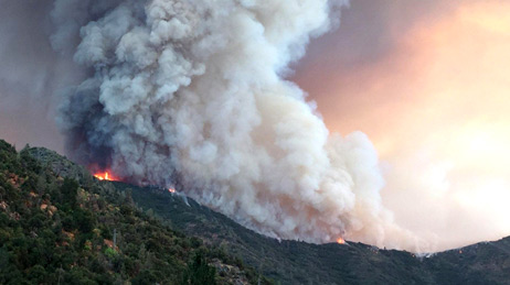 Large plume of smoke over a forested hill of the Ferguson Fire near Yosemite